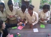 東日本大震災の被災者支援のため折り紙で鶴を折るハイチの少女たち=2011年4月1日、米サンフランシスコの非政府組織「人道のための建築」提供